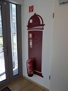Visueller Ablenker bei Weglauftendenz. Die rote Litfasssäule verbigt den roten Feuerlöscher. Gleichzeitig lenkt das Schriftfeld den Blick auf Interessanteres